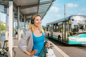 Junge Frau mit Kopfhörer an RSVG-Bushaltestelle
